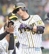 6回、本塁打を放ちナインに迎えられる阪神・上本=甲子園球場(撮影・水島啓輔)