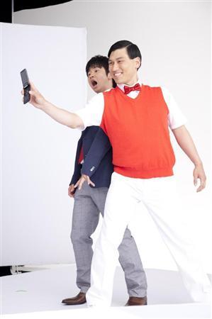携帯を持って笑っている春日と驚いた表情の若林のお笑いコンビ「オードリー」の画像