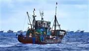 小笠原諸島嫁島の沖合約5キロ付近で目撃された不審船。赤い旗を掲げ、背後にも複数の船が見える=9月22日(父島の住民提供)
