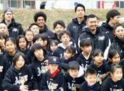 熊本県益城町の仮設住宅を訪問し、地元の児童らと記念撮影するBリーグの選手たち